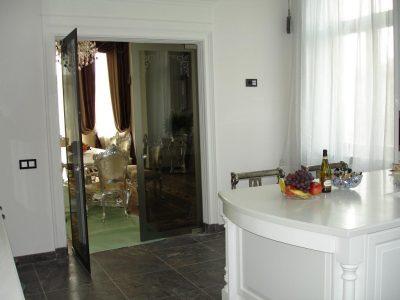 Двухстворчатая стеклянная тонированная дверь разграничивает кухню и столовую