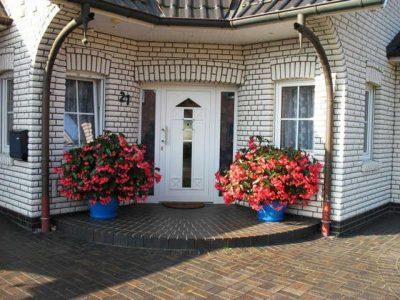 Роскошное крыльцо перед входной дверью частного дома, которое дополнительно декорировано цветами