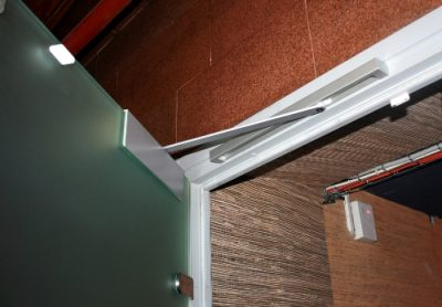 Наддверный тип дверного ограничителя, выступающего в роли фиксатора положения конструкции