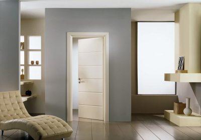 Белая межкомнатная дверная конструкция в сером интерьере, которая гармонично сочетается по цветовой гамме с другими предметами мебели и декора