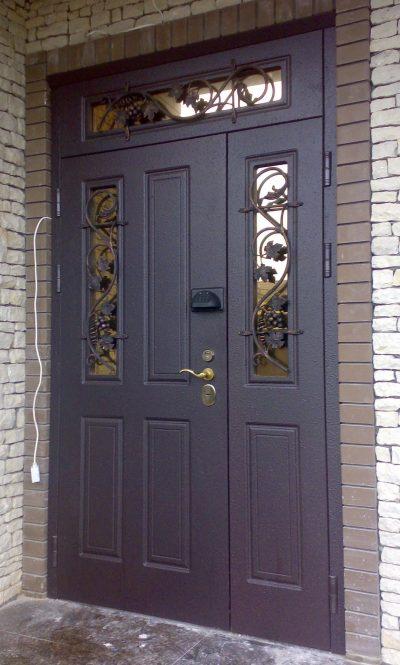 Входные двери из металла, которые дополнены зеркальными вставками и решетками в виде виноградной лозы