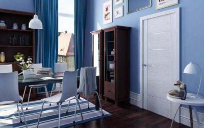 Интерьер в синих тонах со светлой дверью имеет просторную и умиротворенную обстановку