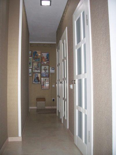 Светлые остекленные дверные полотна делают коридор более просторным