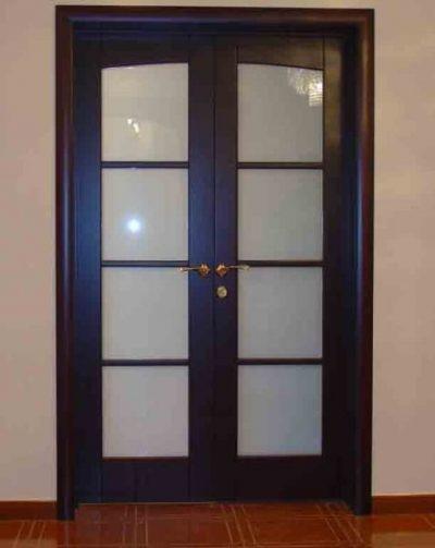 Межкомнатная дверная конструкция распашного типа с двумя створками, оформленная в темной цветовой гамме и дополненная стеклянными вставками