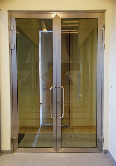 Маятниковая светопрозрачная дверь из нержавеющего профиля
