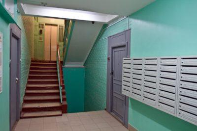 Традиционная площадка перед входными дверями в подъезде, расположенная на лестничном марше одного из этажей многоэтажки